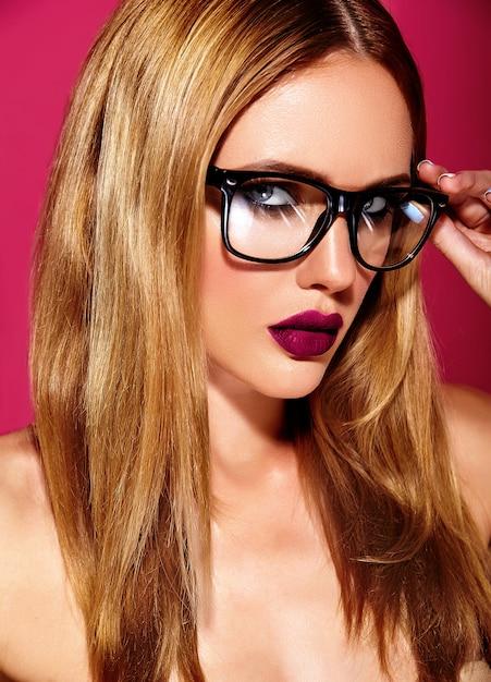 Modèle De Belle Femme Blonde Chaude Avec Un Maquillage Quotidien Frais Avec Des Lèvres Sombres Et Une Peau Saine Et Propre Sur Fond Rouge Dans Des Verres Photo gratuit