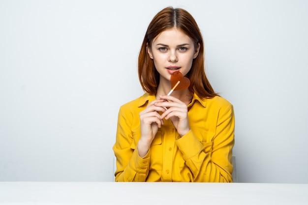 Modèle De Belle Femme Avec Une Sucette Coeur à La Table Dans Une Chemise Jaune Pose Des émotions Différentes. La Saint-valentin Photo Premium