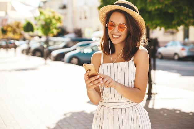 Modèle Brune En Vêtements D'été Posant Dans La Rue à L'aide De Téléphone Portable Photo gratuit