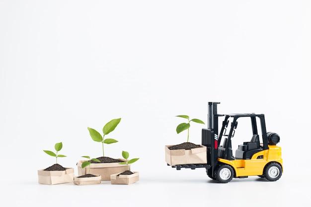 Modèle De Chariot élévateur Miniature, Chargement Des Boîtes En Carton Contenant La Jeune Plante Isolée Sur Fond Blanc. Photo Premium
