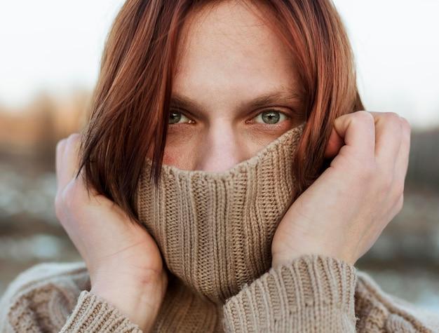 Modèle Couvrant Le Visage Avec Un Pull Beige Photo gratuit