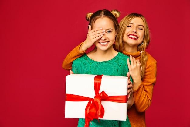 Modèle Couvrant Les Yeux De Son Amie Et Lui Donnant Un Grand Coffret Cadeau Photo gratuit