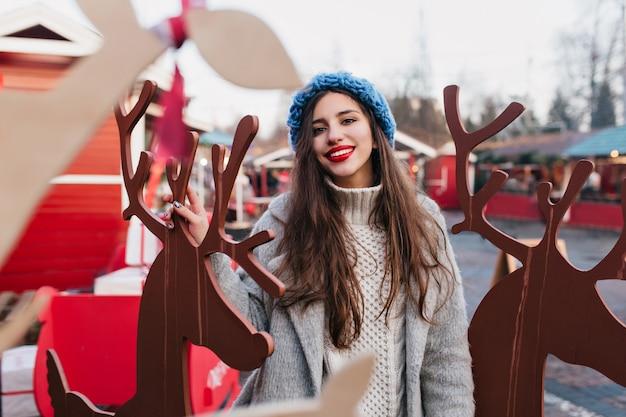 Modèle Féminin Aux Cheveux Noirs Extatique Appréciant Noël Dans Un Parc D'attractions à Thème. Portrait En Plein Air De Fille Heureuse En Bonnet Bleu Tricoté Posant Près De Décoration De Vacances En Hiver. Photo gratuit