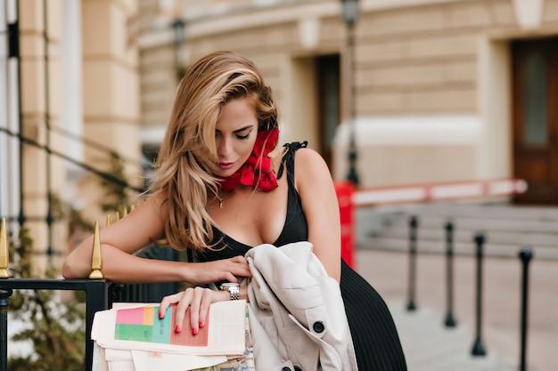 Modèle Féminin Européen Fatigué Regardant Montre-bracelet En Attendant Quelqu'un Dans La Ruelle En Belle Tenue Photo gratuit