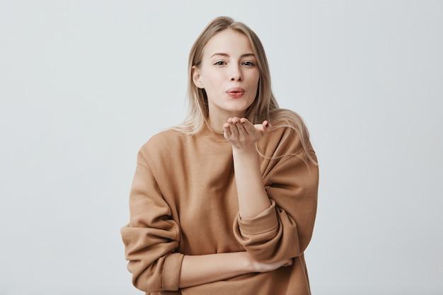 Modèle Féminin Rêveur Attrayant Avec Des Cheveux Blonds Fait La Moue, Envoie Des Baisers Photo gratuit