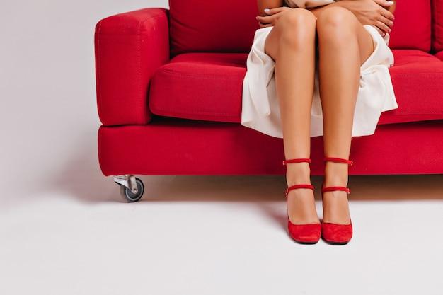Modèle Féminin En Robe Blanche Et Chaussures Rouges Assis Sur Un Canapé. Gracieuse Fille Bronzée Posant Sur Le Canapé. Photo gratuit