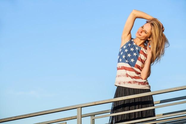Modèle Féminin à La Surface Du Ciel Bleu Dans Un T-shirt Avec Le Drapeau Américain Photo Premium