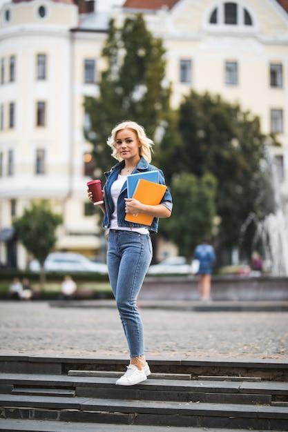 Modèle Fille Blonde Va Aux Classes De Travail Dans Le Centre-ville Tenant Des Ordinateurs Portables Café Dans Ses Mains Le Matin Photo gratuit