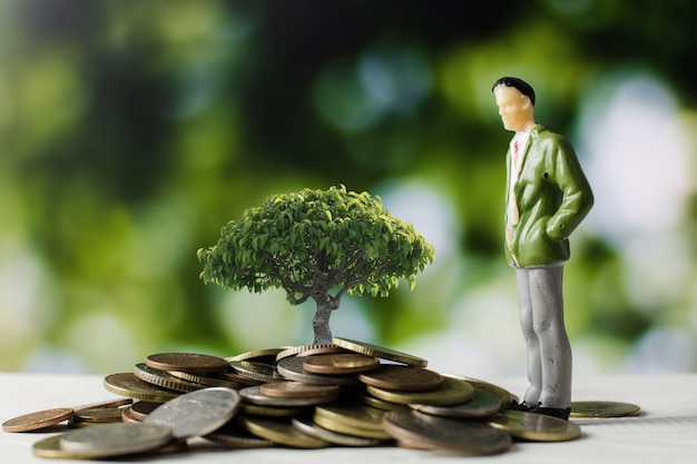 Modèle de gens d'affaires avec des pièces d'argent avec petit arbre en croissance Photo Premium