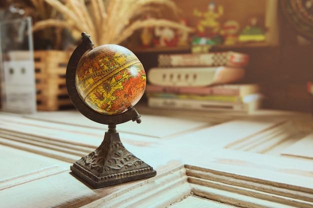 Modèle de globe antique sur table en bois avec la lumière du soleil orange, style vintage. Photo Premium