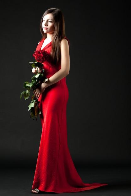 Modèle De Jeune Femme Brune En Robe De Soirée Longue Rouge Debout Et Tenant Le Bouquet De Roses Rouges Dans Les Mains Sur Fond Sombre En Studio Photo Photo Premium