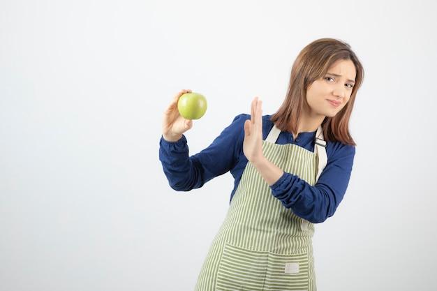 Modèle De Jeune Femme Mignonne En Tablier Refusant D'une Pomme Verte Fraîche. Photo gratuit