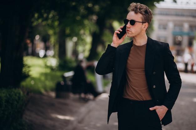 Modèle jeune homme à l'aide de téléphone Photo gratuit