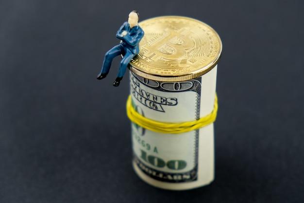 Un modèle de jouet d'homme est assis sur une pièce de monnaie en bitcoins et un rouleau de billets en dollars américains. Photo Premium
