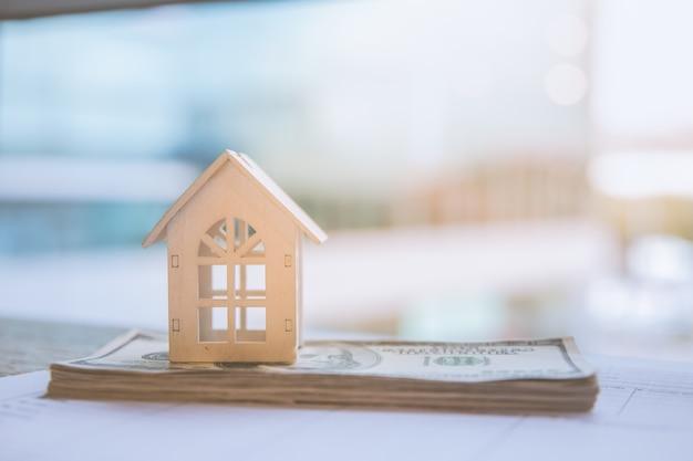 Modèle de maison blanche sur les billets en dollars. concept immobilier d'assurance et d'investissement immobilier. Photo Premium