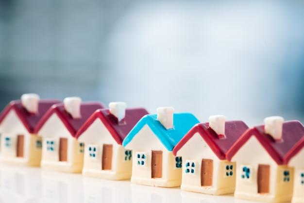 Modèle de maison bleue parmi la maison rouge avec les milieux de la ville. Photo Premium