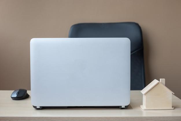 Modèle de maison en bois et ordinateur portable sur la table Photo Premium
