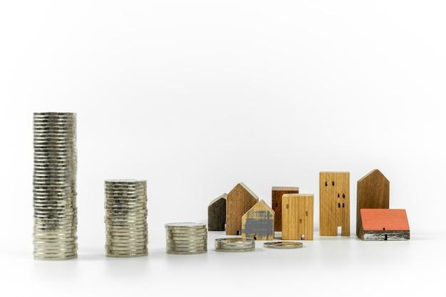 Modèle de maison en bois et rangée de pièces de monnaie sur fond blanc, isoler, Photo Premium