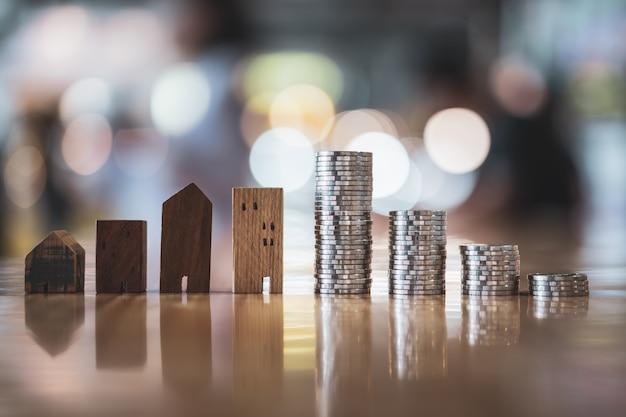 Modèle de maison en bois et rangée de pièces de monnaie sur fond blanc, marché immobilier Photo Premium
