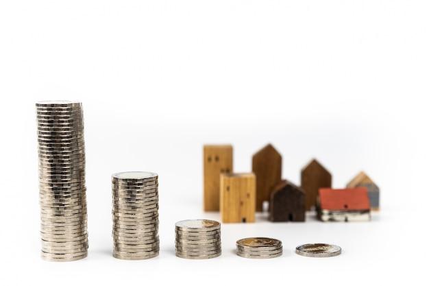 Modèle de maison en bois et rangée de pièces de monnaie sur fond blanc Photo Premium