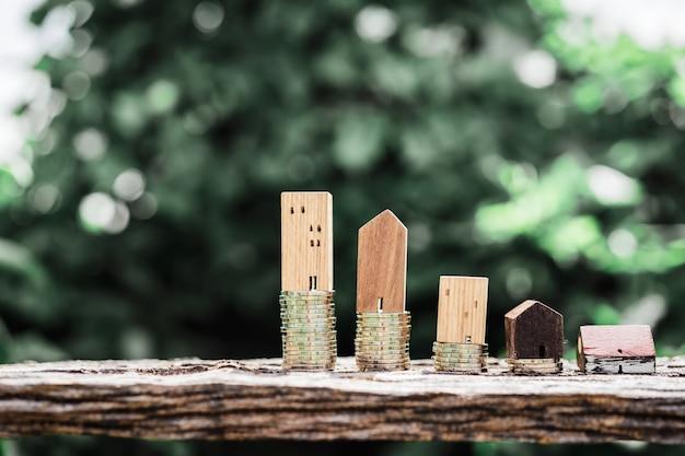 Modèle de maison en bois et rangée de pièces de monnaie sur la table en bois avec backgroud nature lumière. Photo Premium