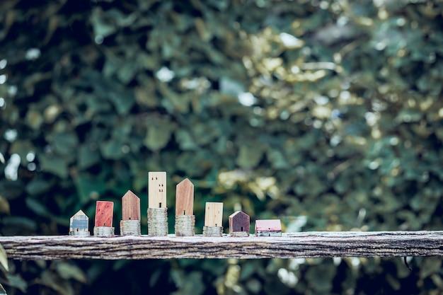 Modèle de maison en bois et rangée de pièces de monnaie sur table en bois avec feuilles vertes flou nature backgro Photo Premium