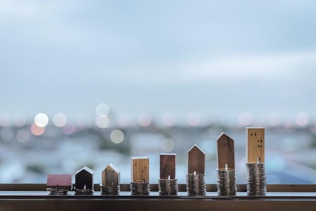 Modèle de maison en bois et rangée de pièces de monnaie sur table en bois avec fond bleu clair, real esta Photo Premium