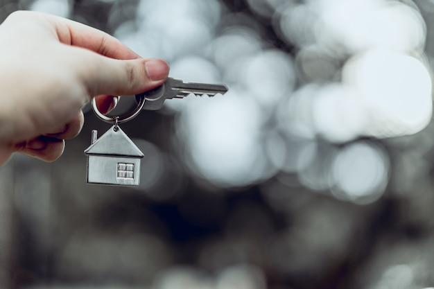 Modèle de maison et clé dans la main de l'agent de courtier d'assurance habitation Photo Premium