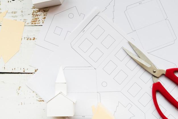Modèle de maison à la main et des ciseaux sur du papier blanc sur la table en bois blanc Photo gratuit