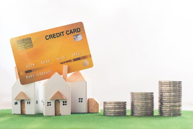 Modèle de maison miniature avec pile de cartes de crédit et de pièces d'argent sur l'herbe de simulation Photo Premium