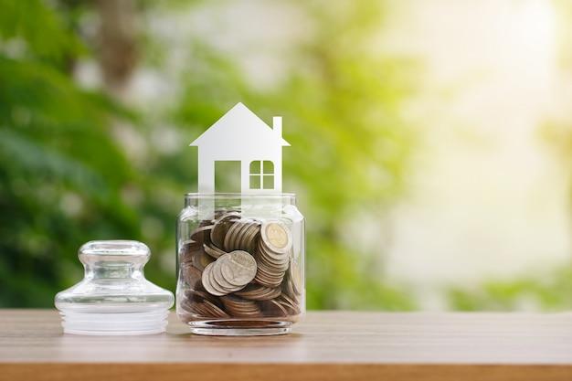 Modèle de maison sur des pièces de monnaie dans un bocal en verre, économiser pour acheter une maison Photo Premium