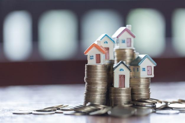 Modèle de maison sur la pile de pièces. concept pour échelle immobilière, hypothèque et investissement immobilier. Photo Premium