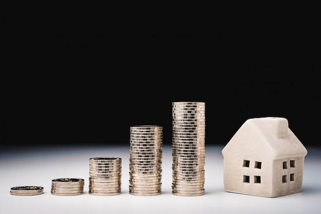 Modèle de maison et rangée de pièces de monnaie sur tableau blanc Photo Premium