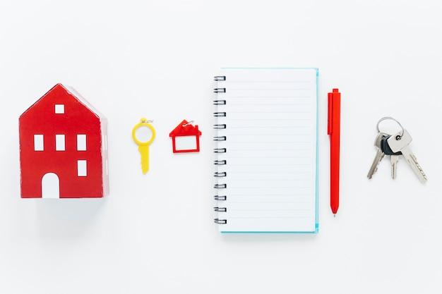 Modèle de maison rouge; clé en plastique; porte-clés en forme de maison; journal en spirale; stylo et touches disposées dans une rangée sur fond blanc Photo gratuit