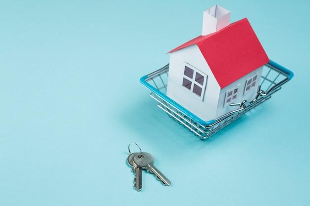 Modèle de maison de toit rouge dans un panier métallique avec des clés sur la surface bleue Photo gratuit
