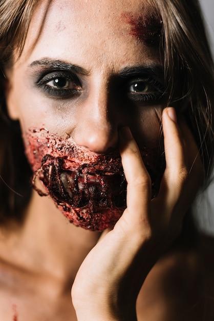 Modèle avec le maquillage de halloween touchant le visage Photo gratuit