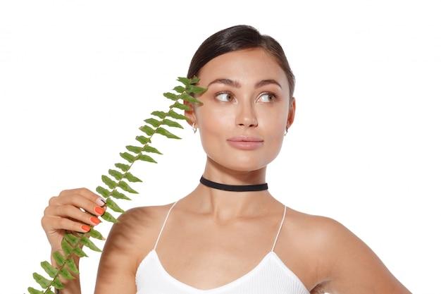 Modèle avec maquillage naturel et feuille verte isolé sur blanc. spa et bien-être. Photo Premium