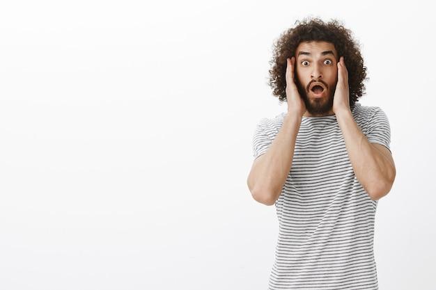 Modèle Masculin Hispanique Surpris Surpris Avec Une Barbe Et Des Cheveux Bouclés, Tenant Des Paumes Sur Les Joues Et Laissant Tomber La Mâchoire D'étonnement Et De Peur Photo gratuit