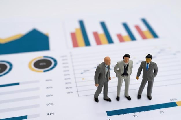 Modèle miniature de gens d'affaires de co-investissement debout sur le graphique de rapport d'entreprise Photo Premium