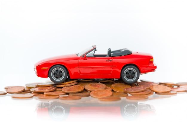 Modèle de parking rouge sur la pile de pièces de monnaie dorées - isolé sur fond blanc. Photo Premium