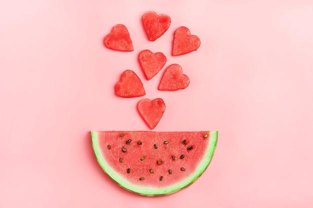 Modèle de pastèque rouge. mise en page créative faite en forme de coeur de melon d'eau sur rose. Photo Premium