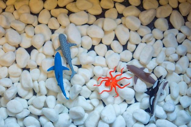 Modèle de poisson artificiel ou faux sur la pierre blanche. Photo Premium
