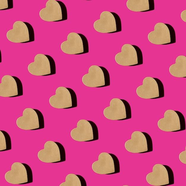 Modèle Sans Couture De Boîte-cadeau Artisanal En Forme De Coeur Sur La Vue De Dessus De Fond Rose Mise à Plat. Composition Créative Pour La Saint-valentin. Photo Premium