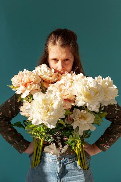 Modèle Sérieux Posant Avec Des Fleurs Photo gratuit