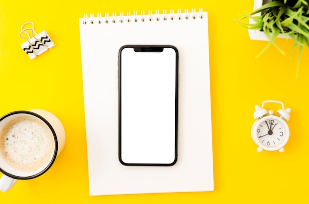 Modèle de smartphone de la vue de dessus sur l'espace de travail Photo gratuit