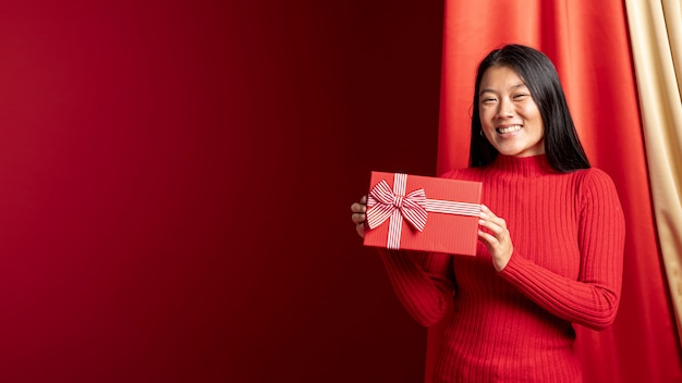 Modèle tenant une boîte-cadeau pour le nouvel an chinois avec espace de copie Photo gratuit