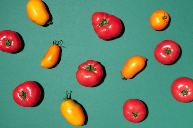 Modèle de tomates jaunes et rouges sur fond vert Photo Premium