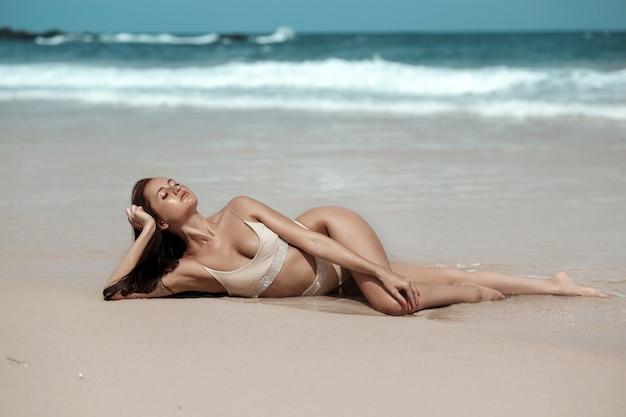 Un modèle tropical avec des taches de rousseur sur son visage et portant un bikini beige reposant sur la mer Photo Premium