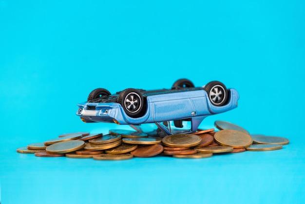 Modèle de voiture bleue renversé la composition sur la pile de pièces d'or Photo Premium