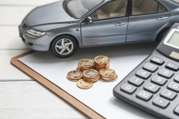 Modèle de voiture, calculatrice et pièces de monnaie sur table blanche Photo gratuit
